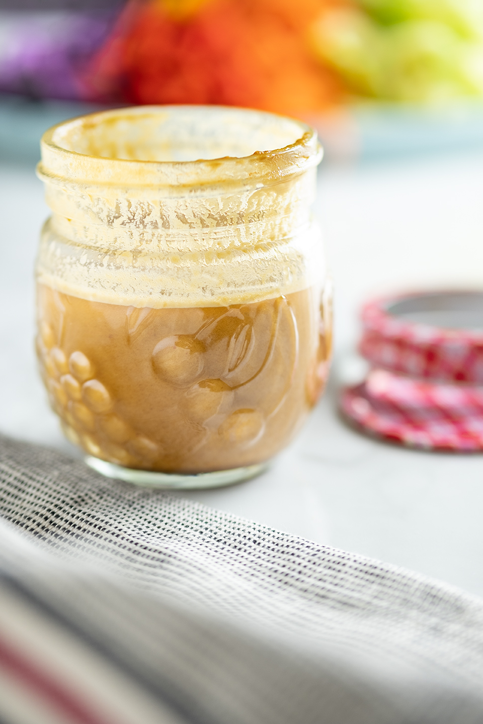 Sunbutter dressing in a small glass canning jar with red lid and vegetables in the background.
