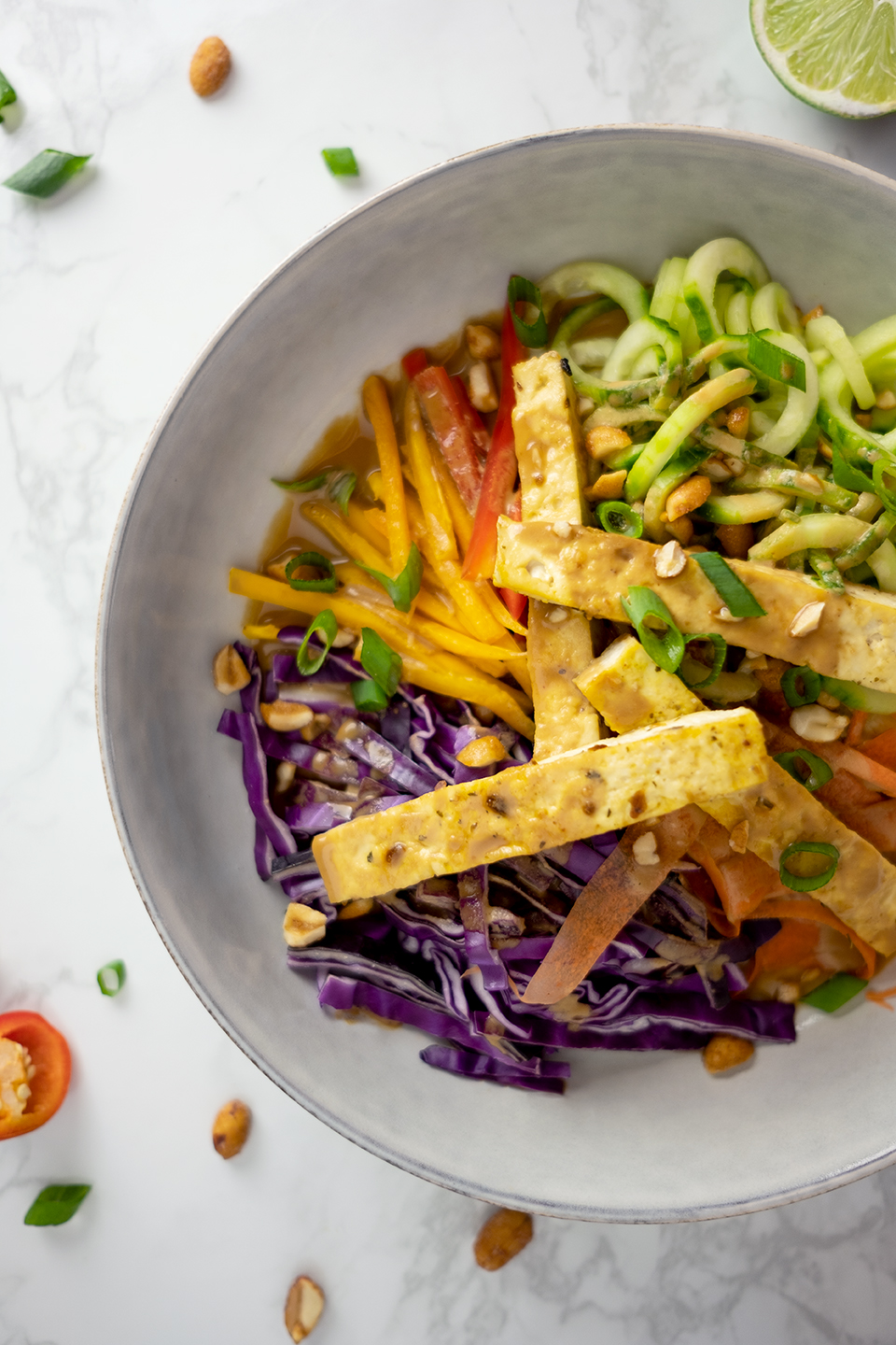 Thai vegetarian salad with sunbutter dressing and tofu in a gray ceramic bowl.