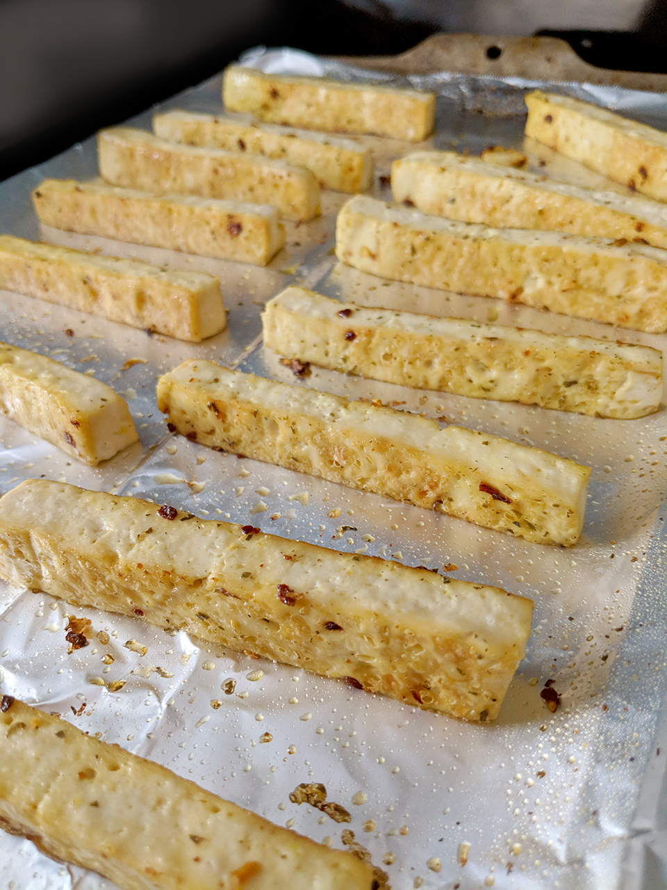 Baked strips of tofu on an aluminum tray.