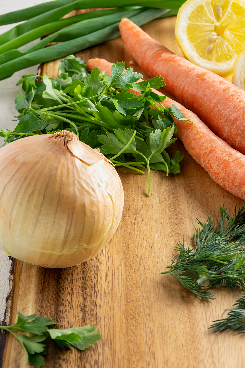 Ingredients for soup, Onions, Carrots, Scallions, Lemon, Parsley and Dill on a wooded board.