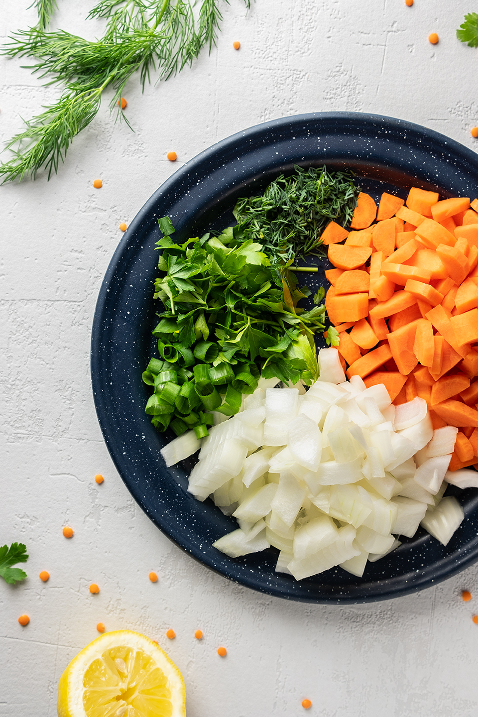 Ingredients for soup, Onions, Carrots, Scallions, Lemon, Parsley and Dill.  Chopped on a plate.