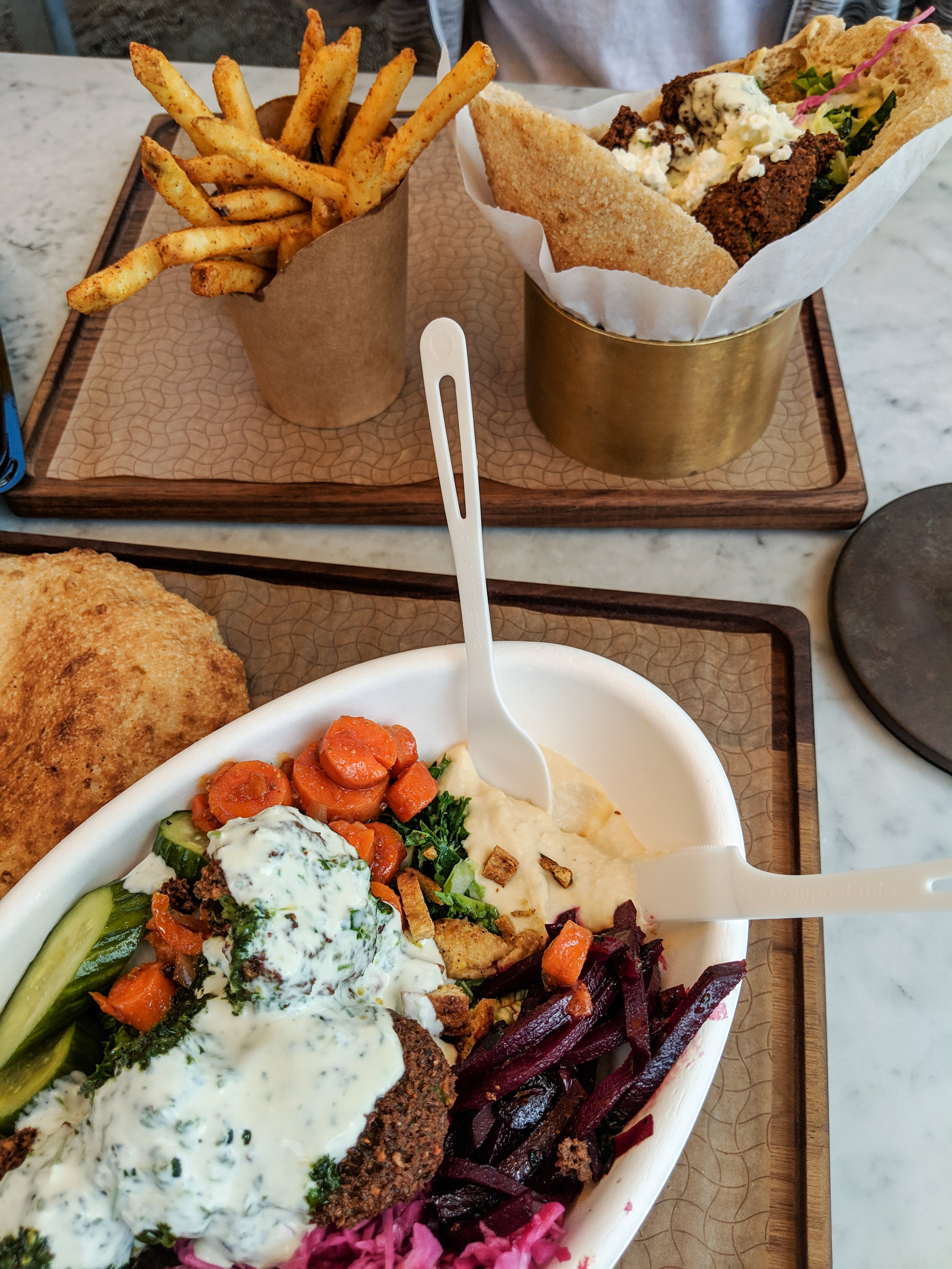 Falafel Salad with carrots, hummus, baba and pickles from Brassica. Falafel Sandwich and fries with special sauce.