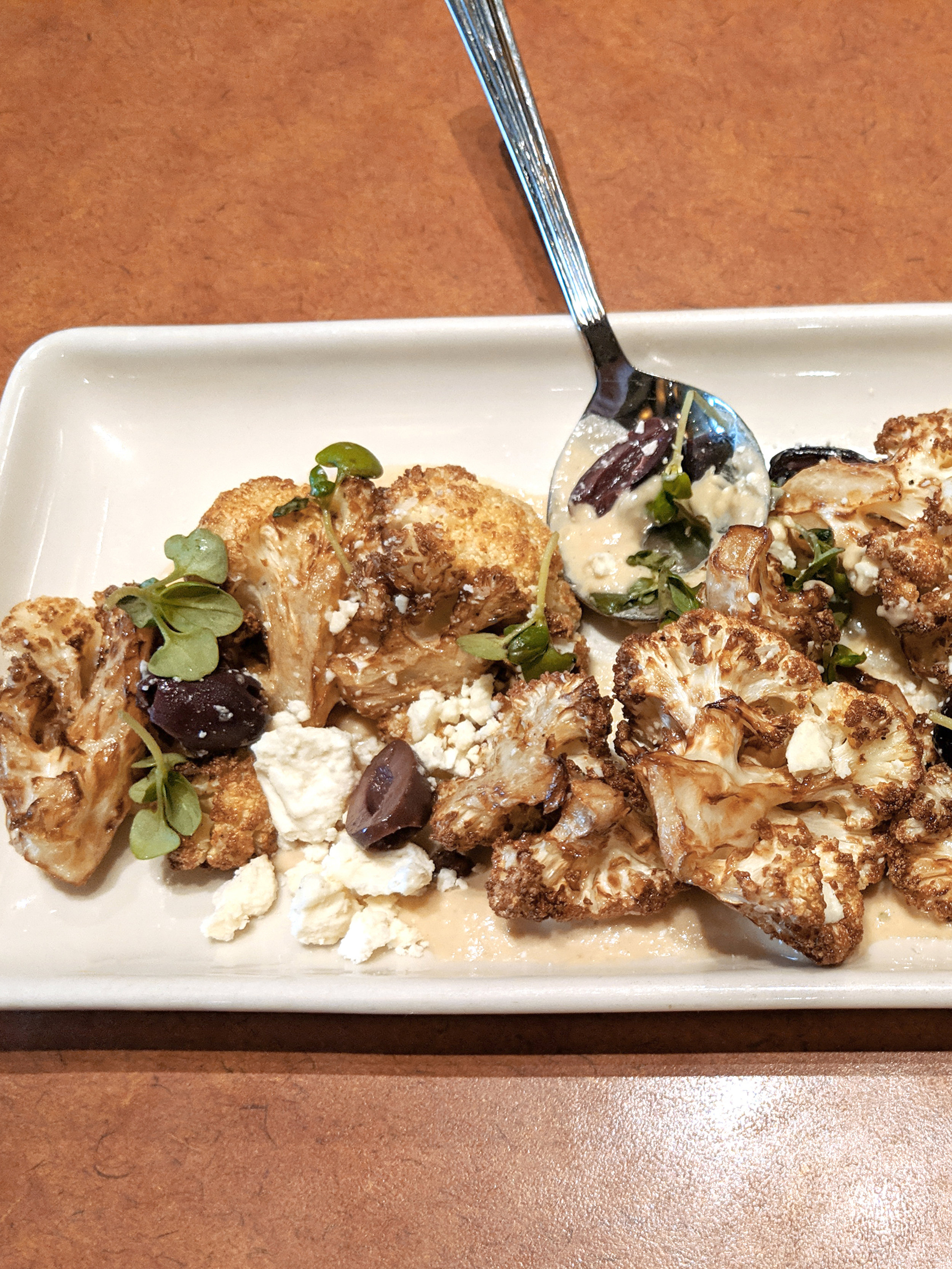 Crispy Cauliflower from Nordstom's on a long white plate with olives and tahini sauce.