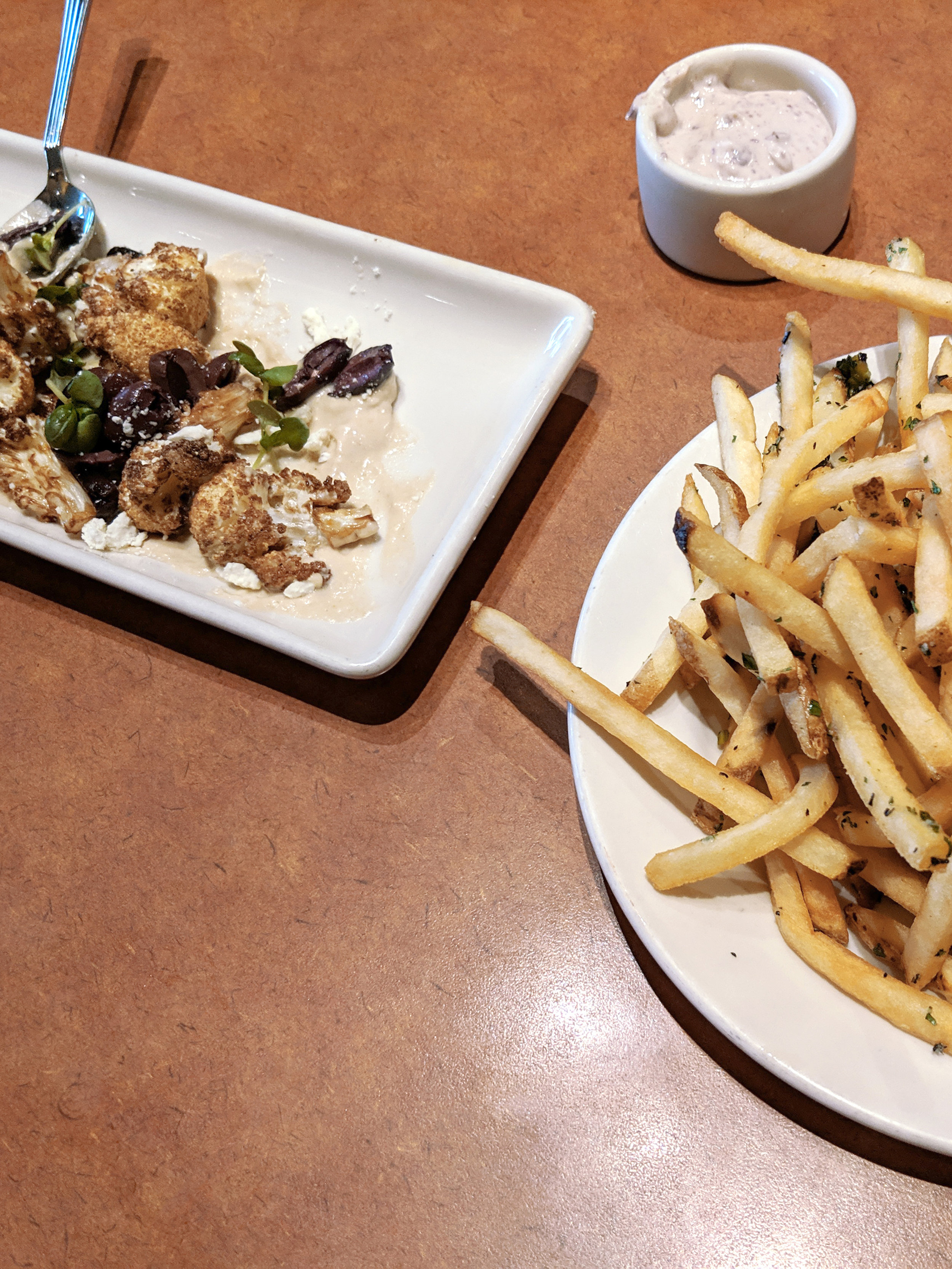 Crispy Cauliflower from Nordstom's on a long white plate with olives and tahini sauce. Kalamata Olive Aioli and french fries.