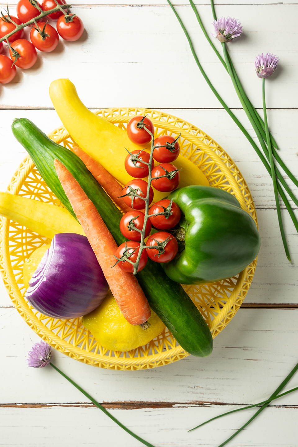 Chives, Green Peppers, Tomatoes, Red Onions, Carrots, Lemons, Cucumber and Summer Squash in a yellow plastic basket.