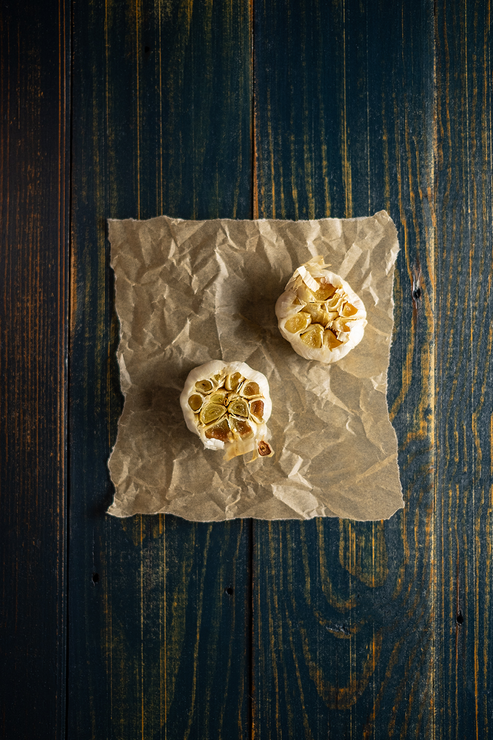 Two heads of roasted garlic on a brown piece of parchment paper.  On a rustic blue wooded background.