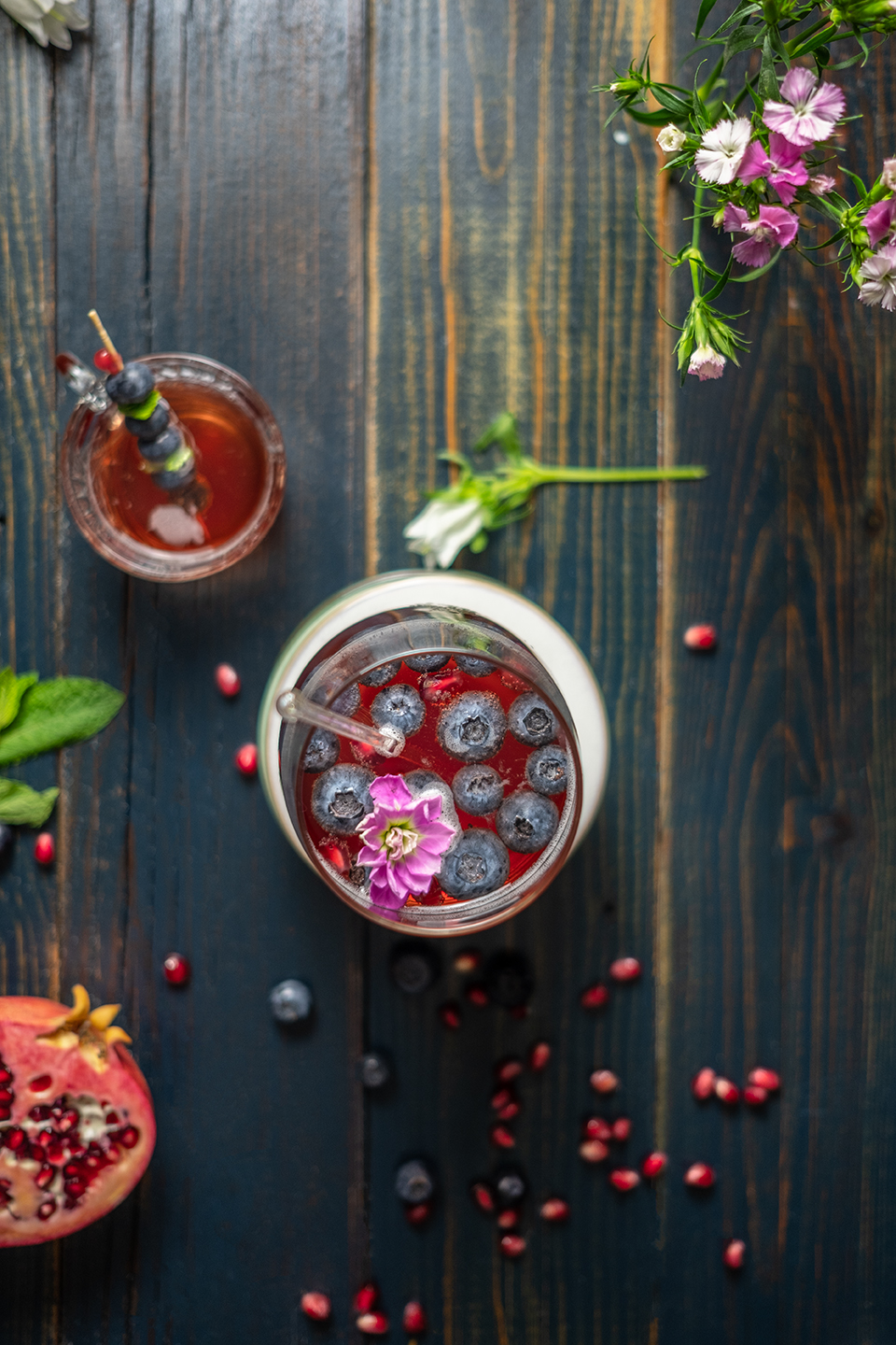 Kenny Cocktail with black tea and pomegranate juice in two glasses on a blue wood background with flowers.