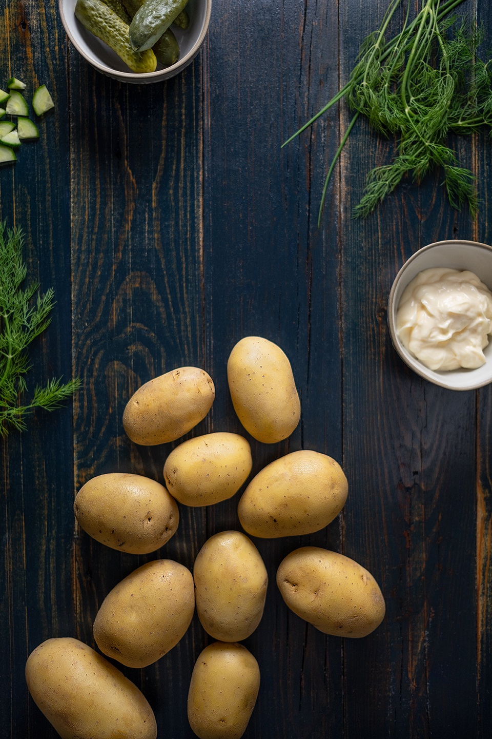 Potatoes, mayonnaise, dill and small pickles on a rustic blue background.