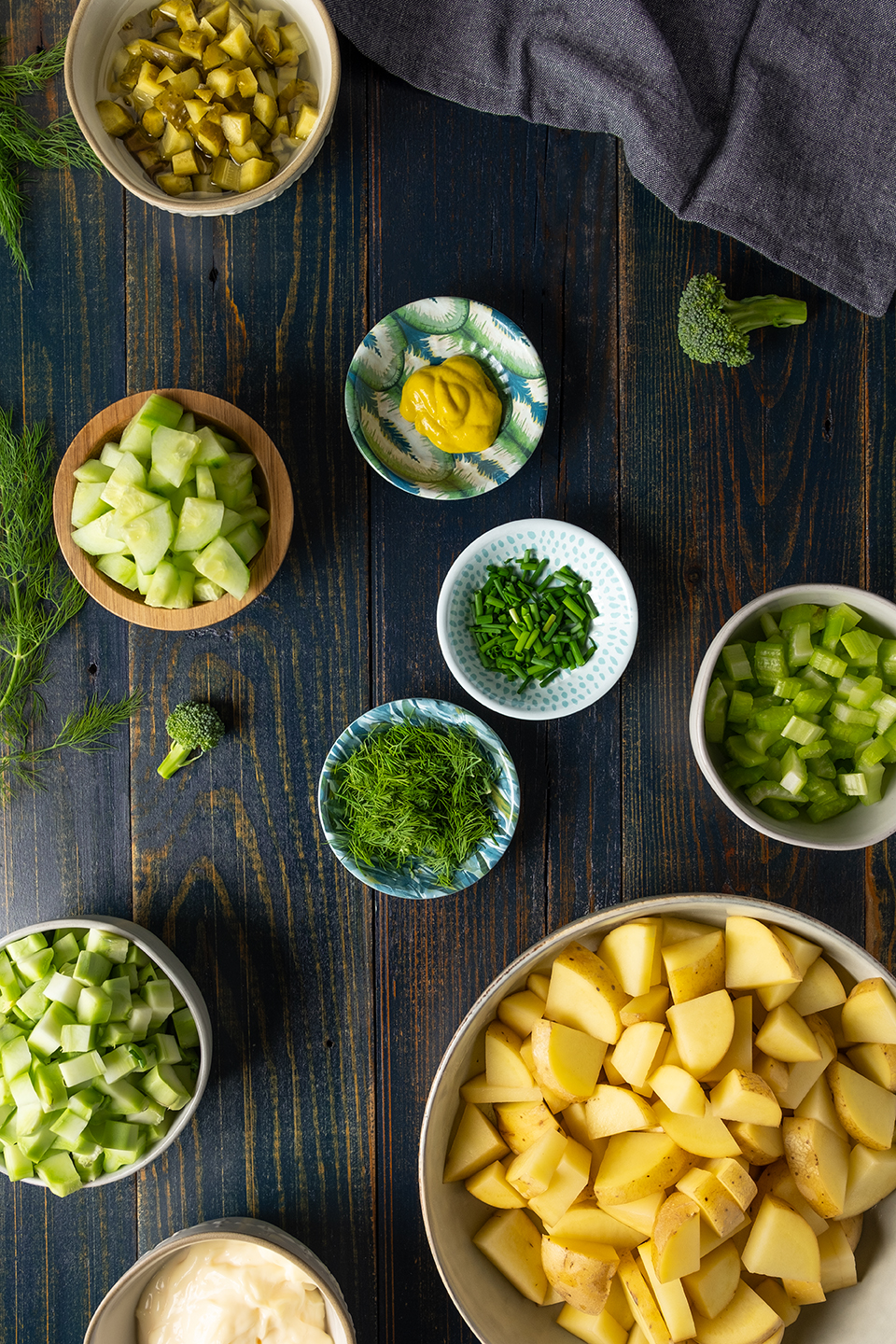 Cubed potatoes, celery, broccoli stems, dill, cucumber, mustard, chive and pickles on a rustic blue wooded background.  Navy napkin.