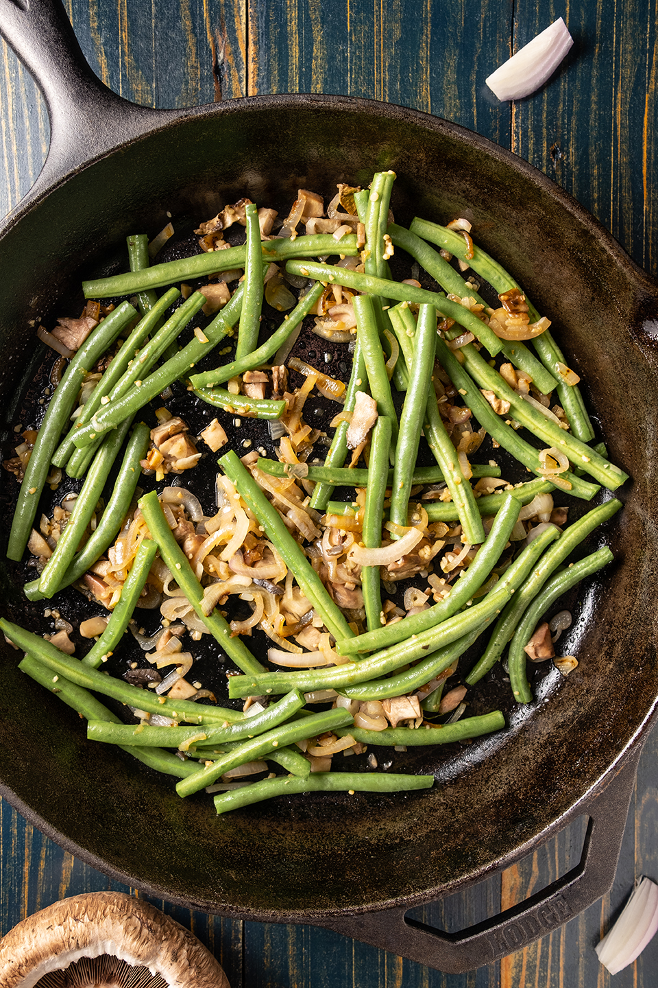 Cooked green beans, shallots and mushrooms in a cast iron pan on a blue wooded background.