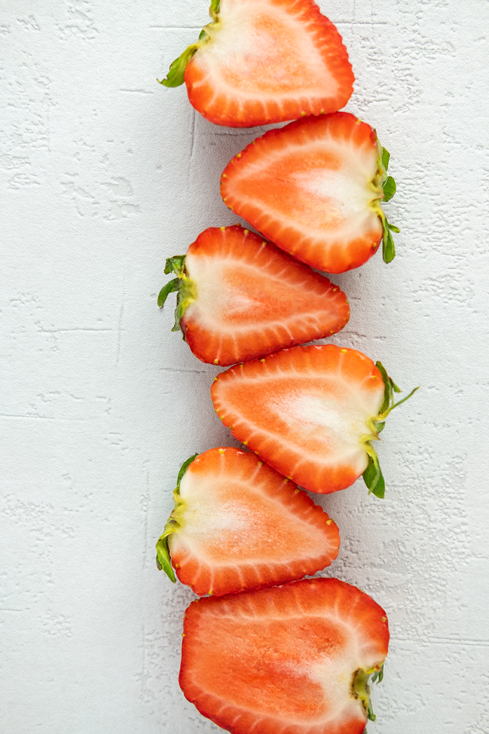 Six strawberries sliced in half on a white background.