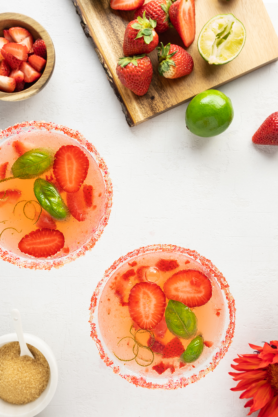 Strawberry basil cocktail in two glasses with red sugar rim.  Chopped strawberries on a cutting board with limes on a white background.