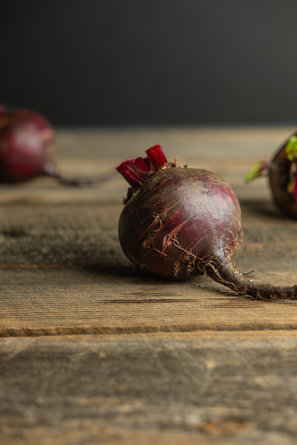Washed raw red beet on a rustic barnwood background.