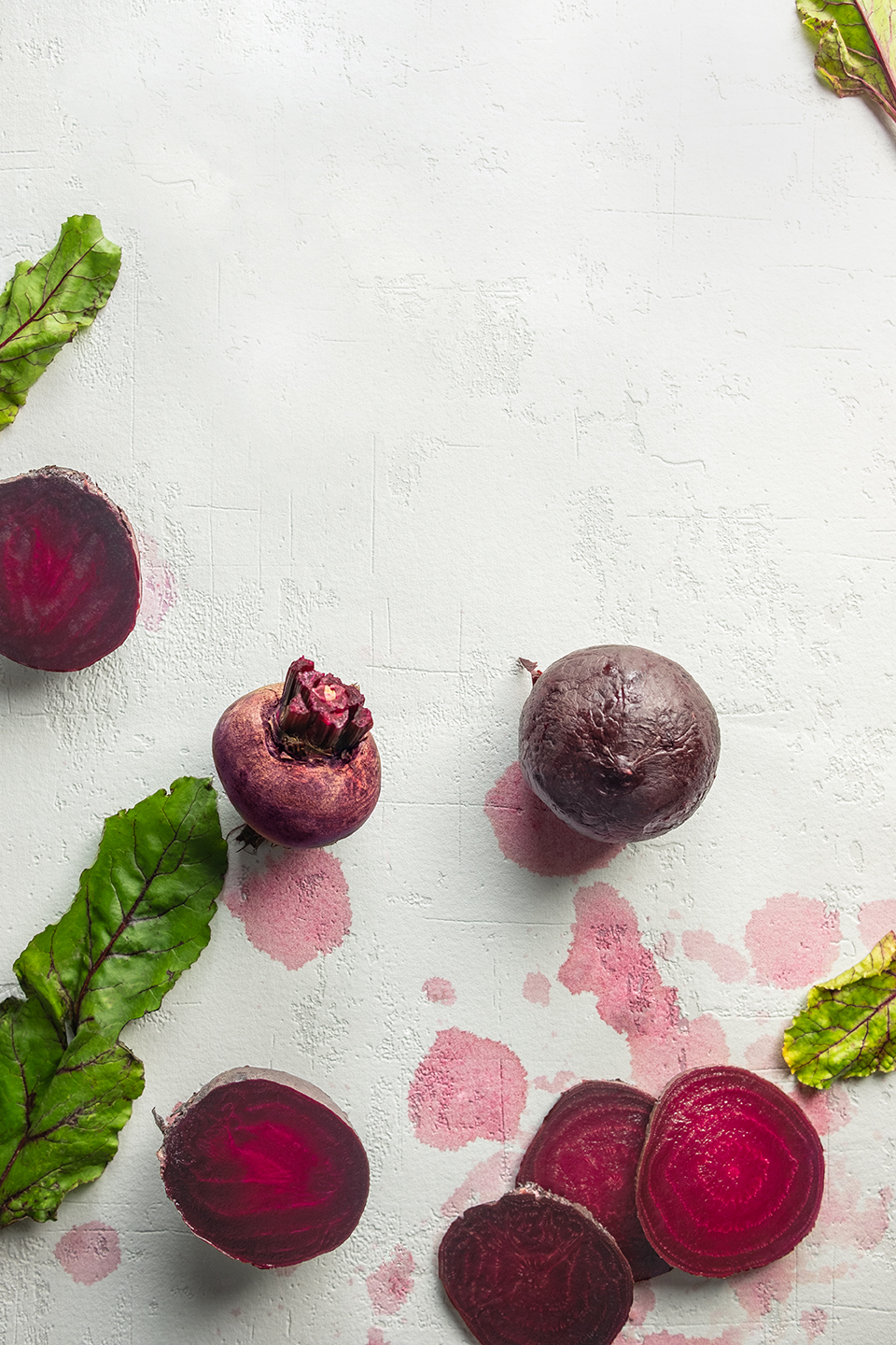 Sliced raw and roasted beets on a white background stained by beet juice.