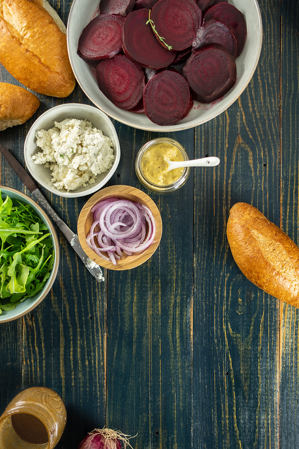 Roasted beets, honey goat cheese spread, onions, mustard, arugula and rolls on a rustic blue background.