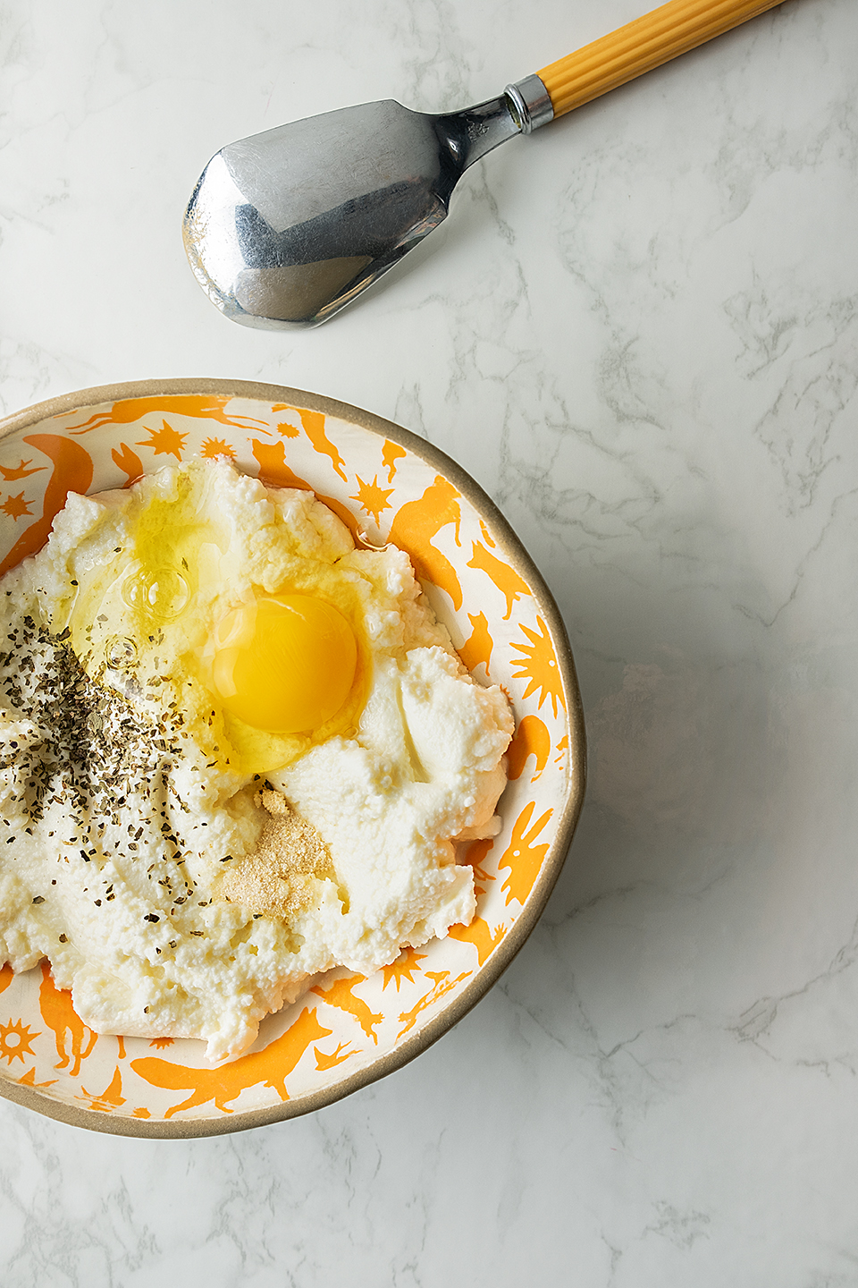Orange bowl with fat free ricotta, egg and seasoning on a marble background with vintage spoon.