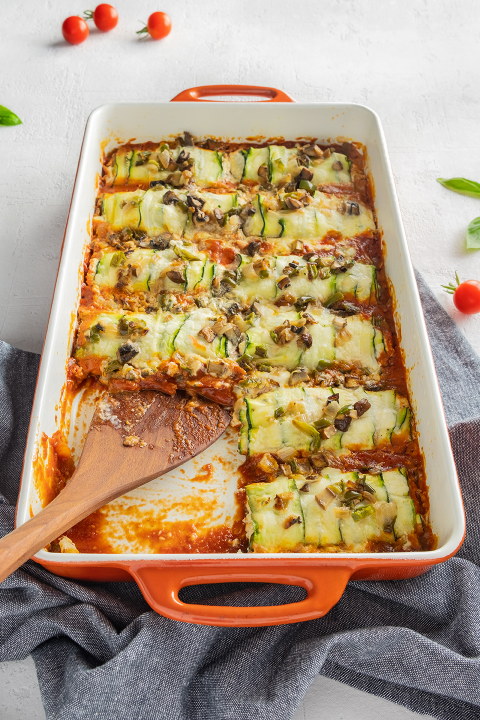 Low carb zucchini and ricotta cannelloni in a orange baking dish.  Cherry tomatoes, basil and blue napkin on a white background.