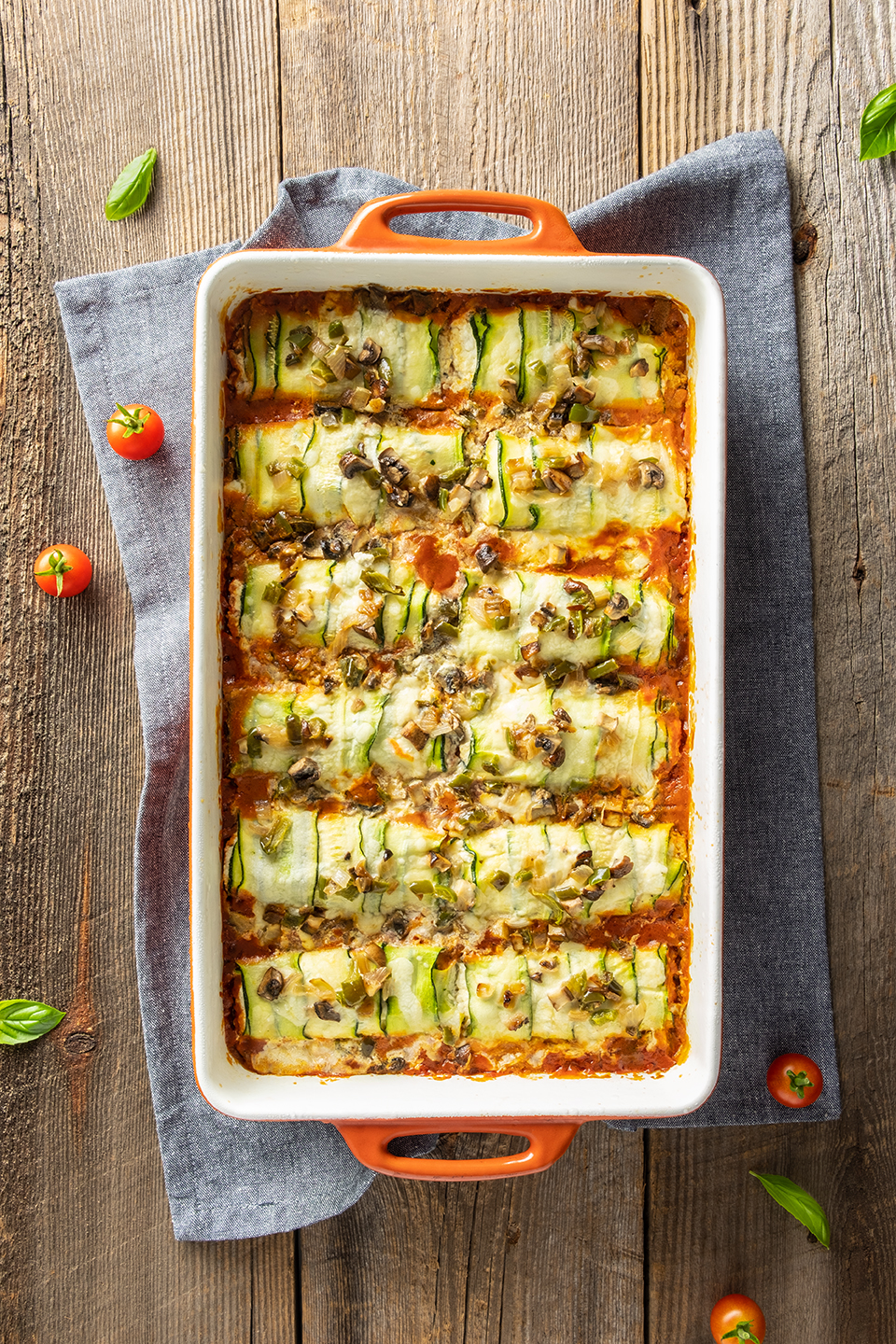 Low carb zucchini and ricotta cannelloni in a orange baking dish with a blue napkin.  Basil and cherry tomatoes on a rustic wooden background.