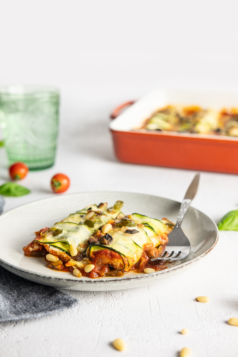 Two Low carb zucchini and ricotta cannelloni served on a grey salad plate.  Casserole dish in background with ice water in a green glass.