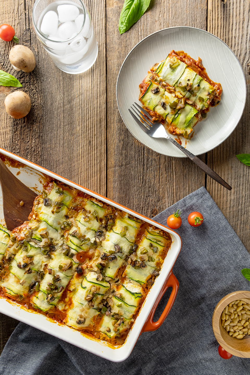 Low carb zucchini and ricotta cannelloni and grey plate with glass of ice water and mushrooms.