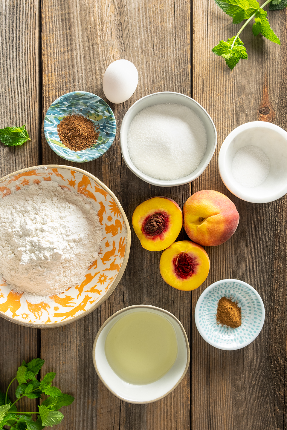 Ingredients for Classic Peach Crisp; flour, eggs, cinnamon, nutmeg, peaches, sugar and oil. Mint leaves on a rustic wooden background.