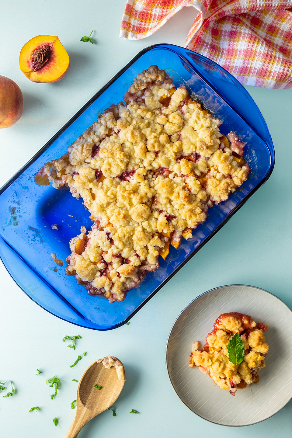 Classic Peach Crisp from Pennsylvania Grange in blue baking dish with peaches and mint.  Oranges checkered napkin on a sea blue background.