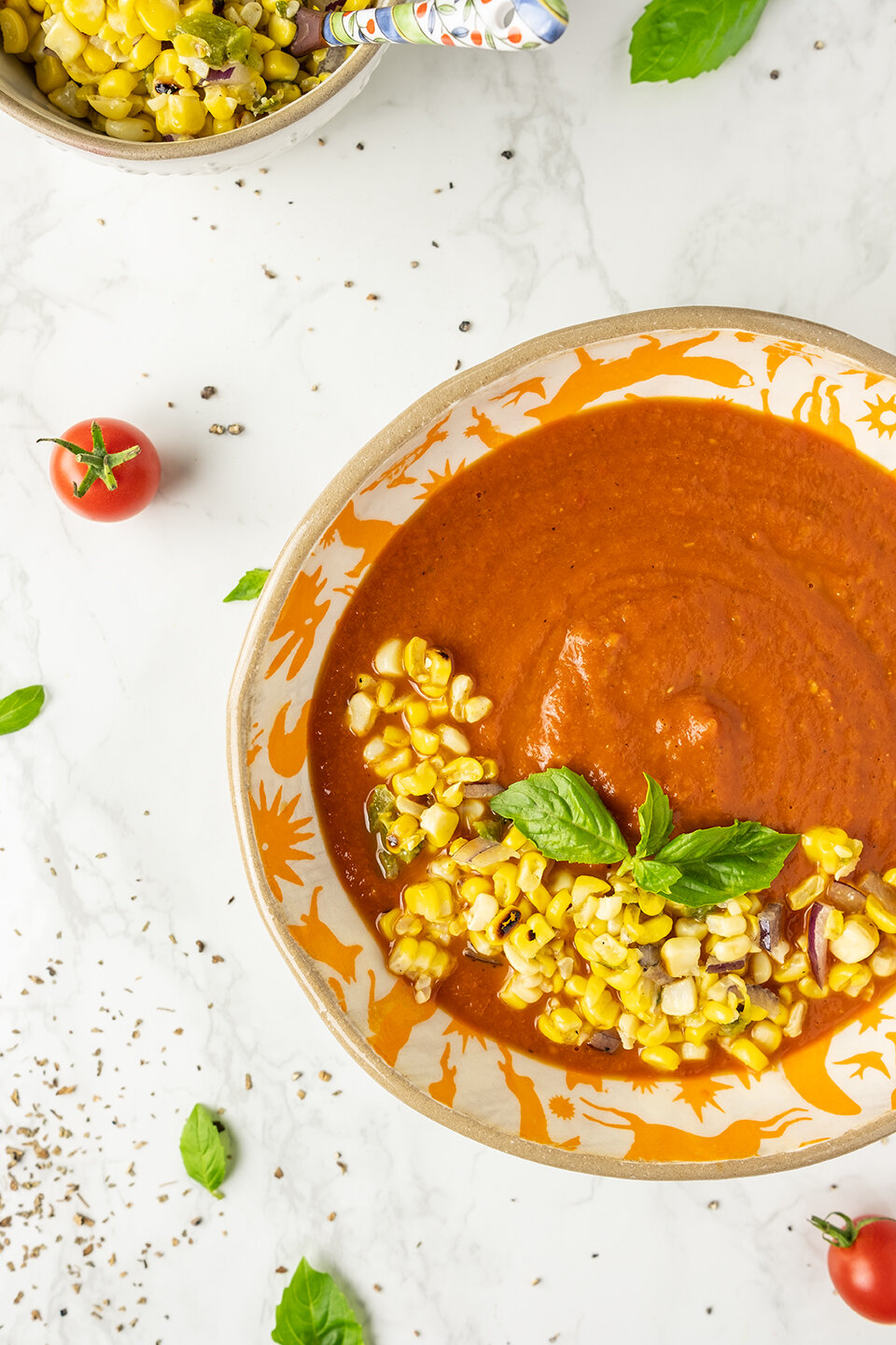 Fresh Tomato Soup with Corn Relish on a marble background. Tomatoes and basil in the background.  Bowl of corn relish with small spoon.