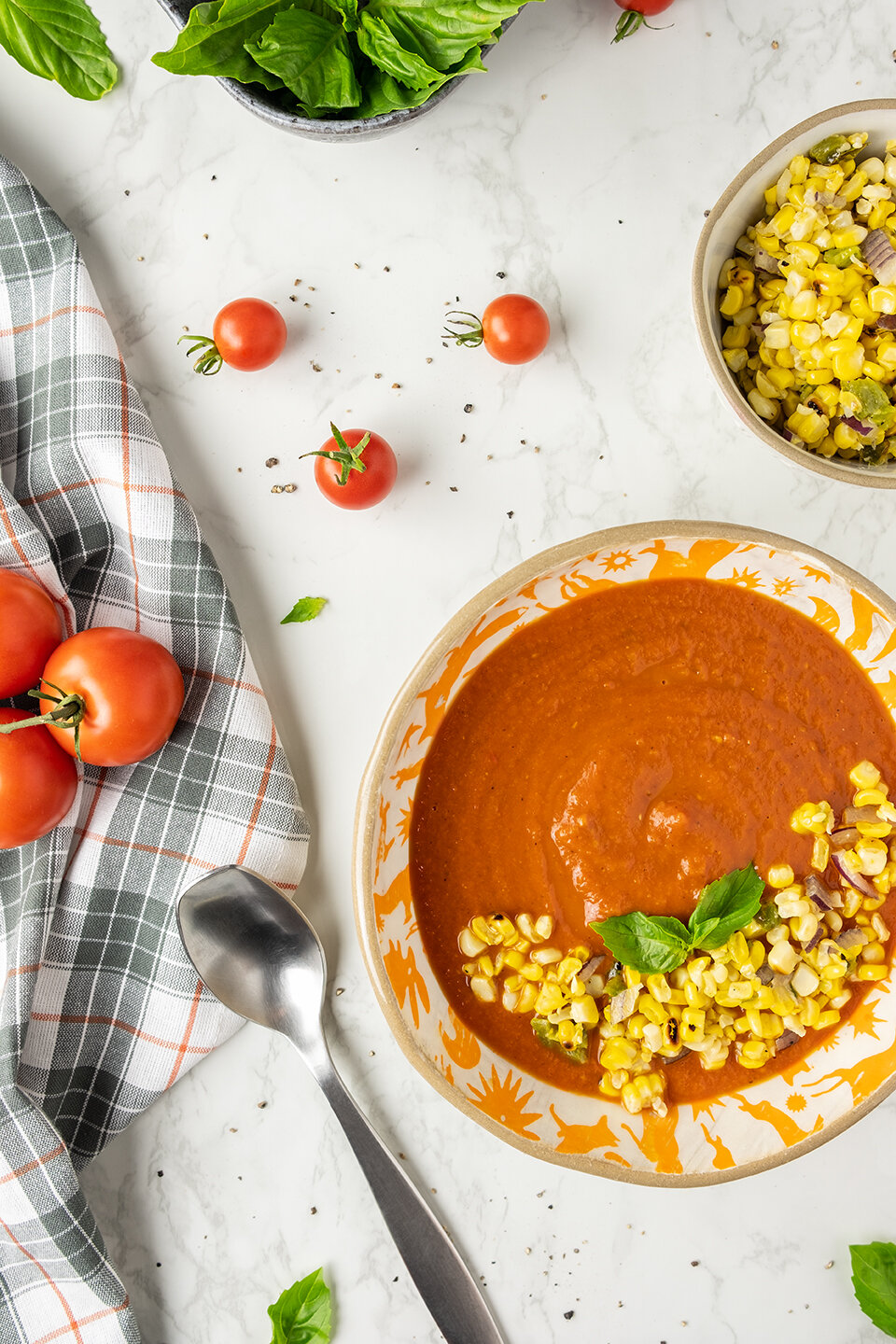 Fresh Tomato Soup with Corn Relish on a marble background.  Tomatoes and basil in the background.
