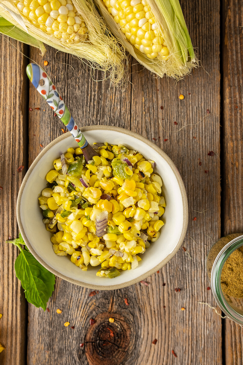 Small bowl of corn relish with colorful spoon and corn on the cob.