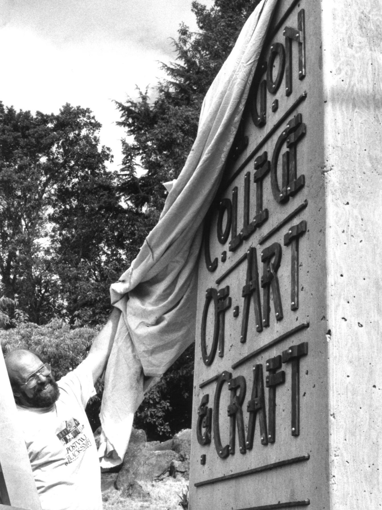 Fire Mountain Forge artist Darryl Nelson installs the new OCAC sign on Barnes Road, September 1996. (OCAC / Heather Watkins)