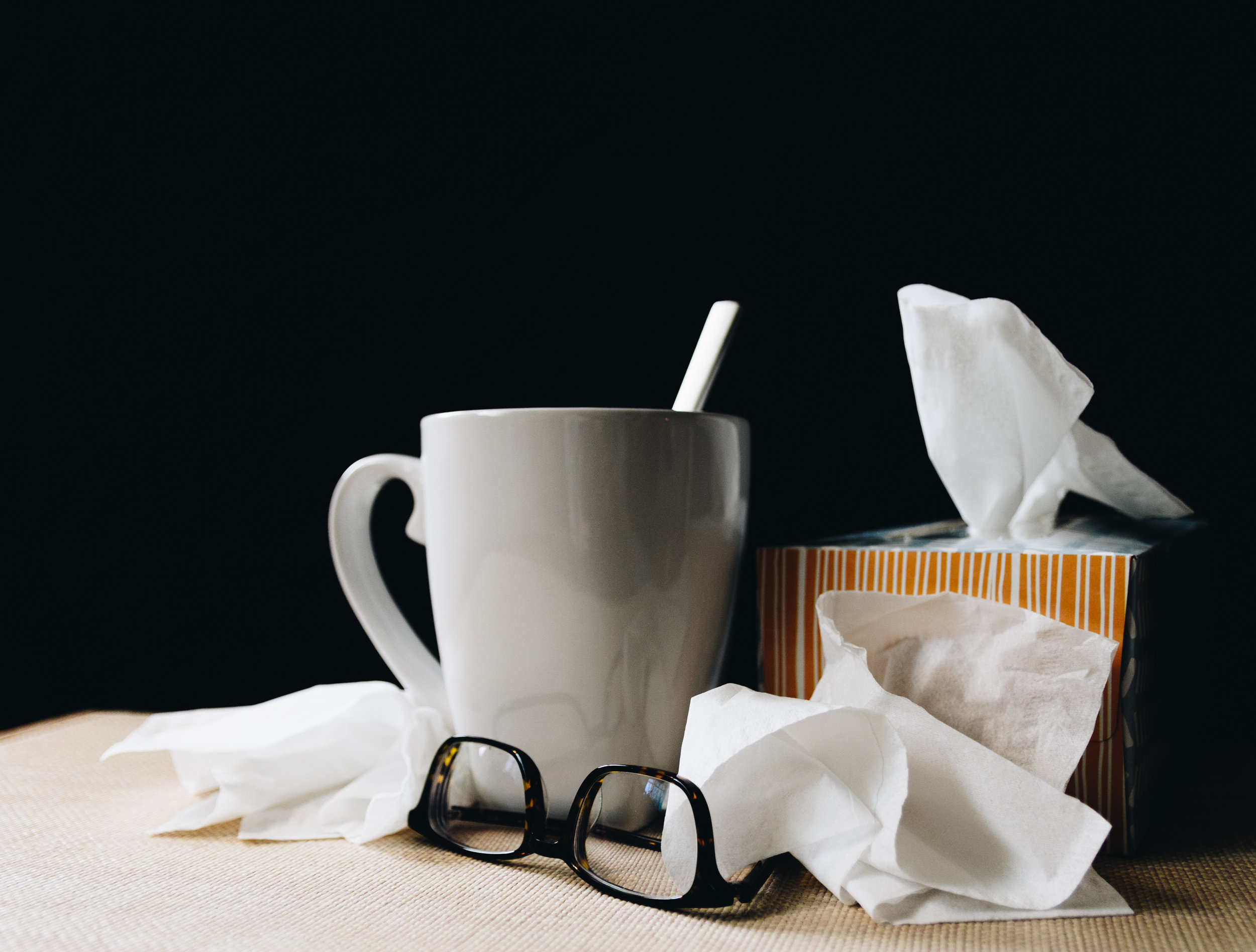 Used tissues, a box of Kleenex, and a cup of tea