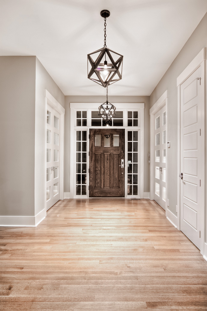 dark wood exterior entrance door surrounded by white-framed windows