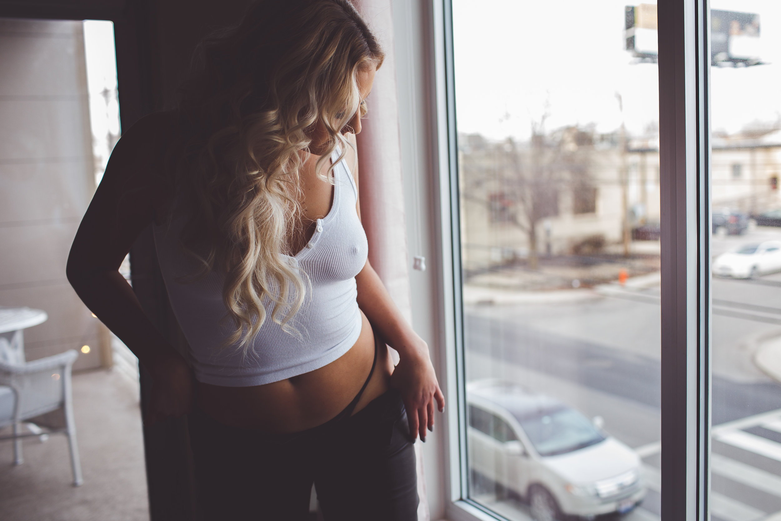 Columbus-Ohio-Boudoir-Photos-Ohio-intimate-womxn-portrait-photographer-woman-wearing-black-leather-white-tank-pulls-down-pants-revealing-hip-pretty-long-blonde-hair-extensions-window-street-marcyharrisortiz.jpg