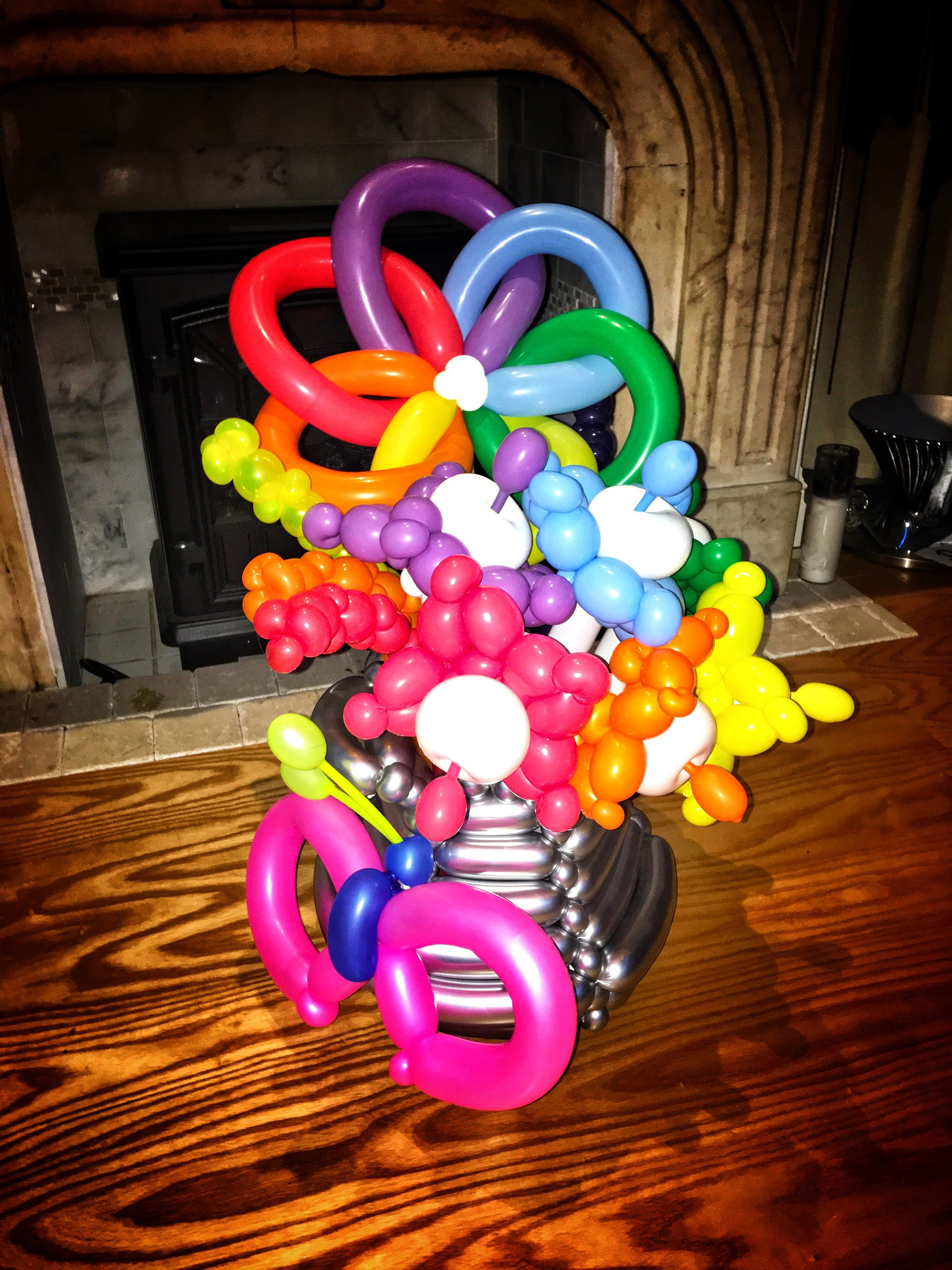 Bouquet. Whimsical bouquet in vibrant rainbow in woven balloon vase and butterfly accent.jpg
