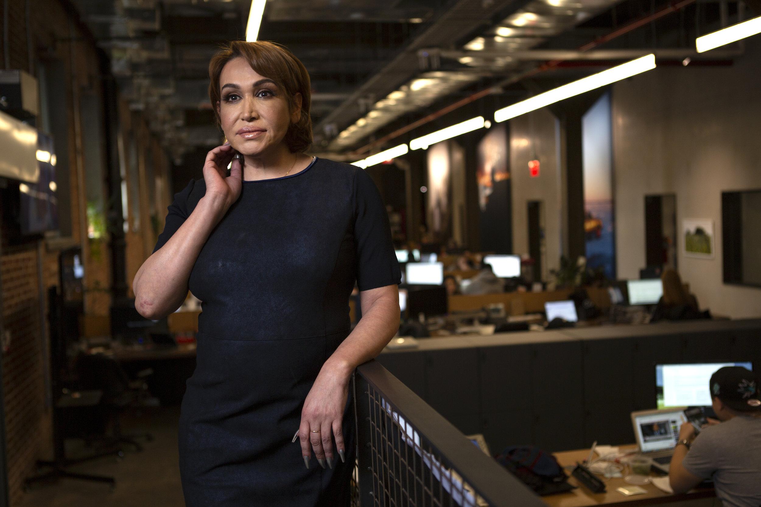 A transgender woman in business attire in an office.jpg
