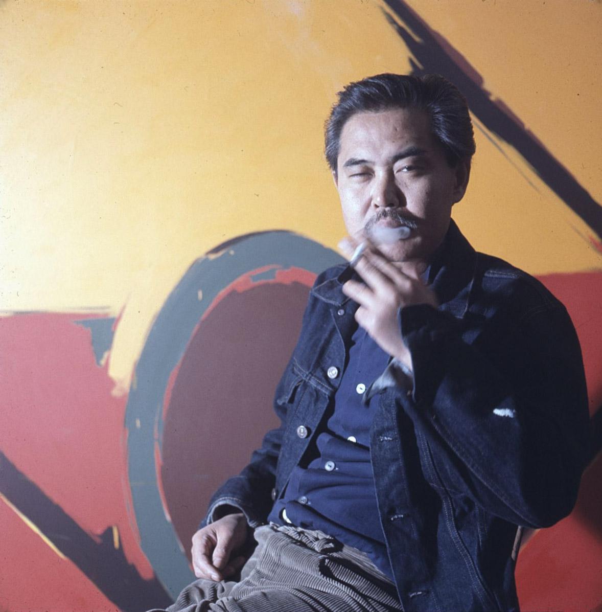 """Kanemitsu smoking in front of the painting """"Range,"""" 1964."""