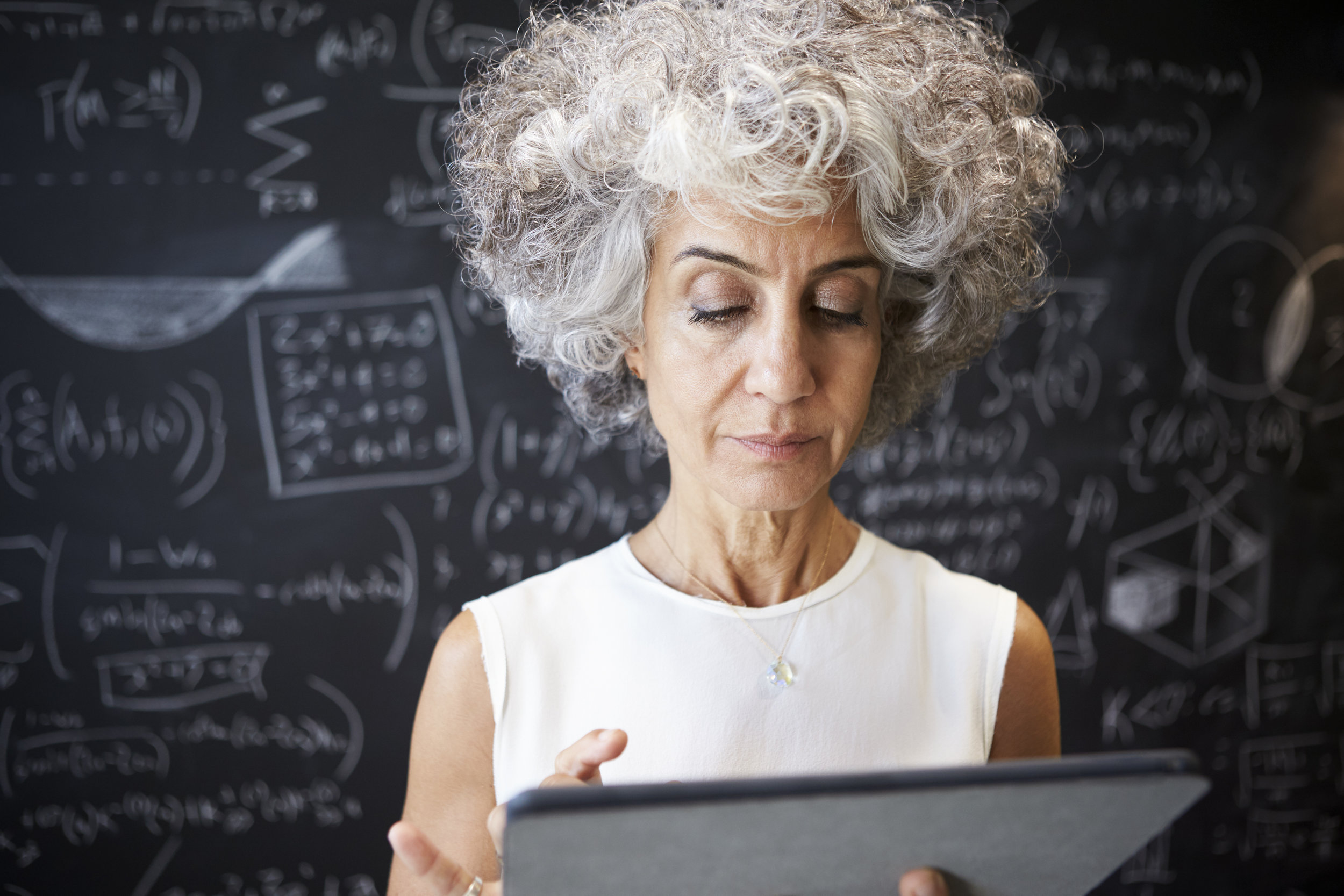 middle-aged-academic-woman-using-tablet-close-up-PC86U9P.jpg