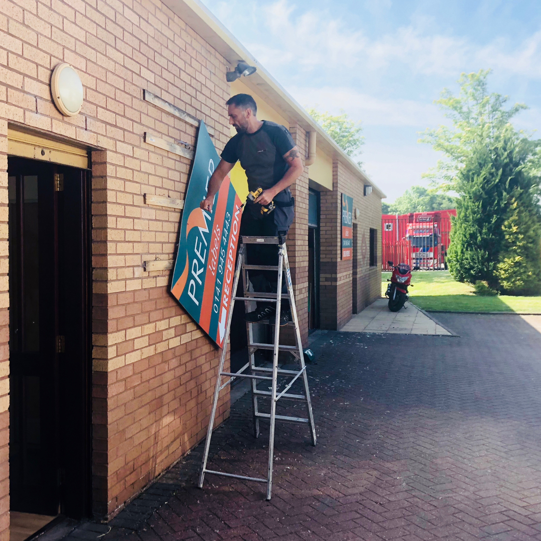 Removing old signage at Premier Labels
