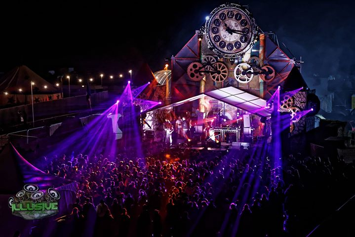 Purple lit festival stage with clockwork.