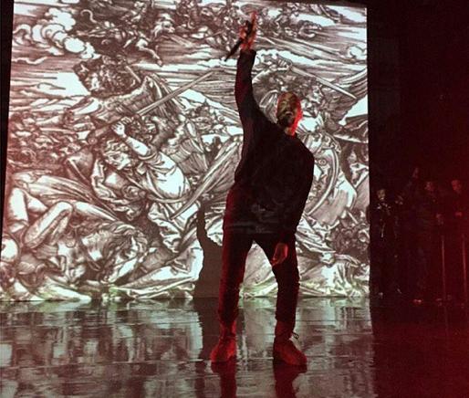 Kanye west holding the mic up.