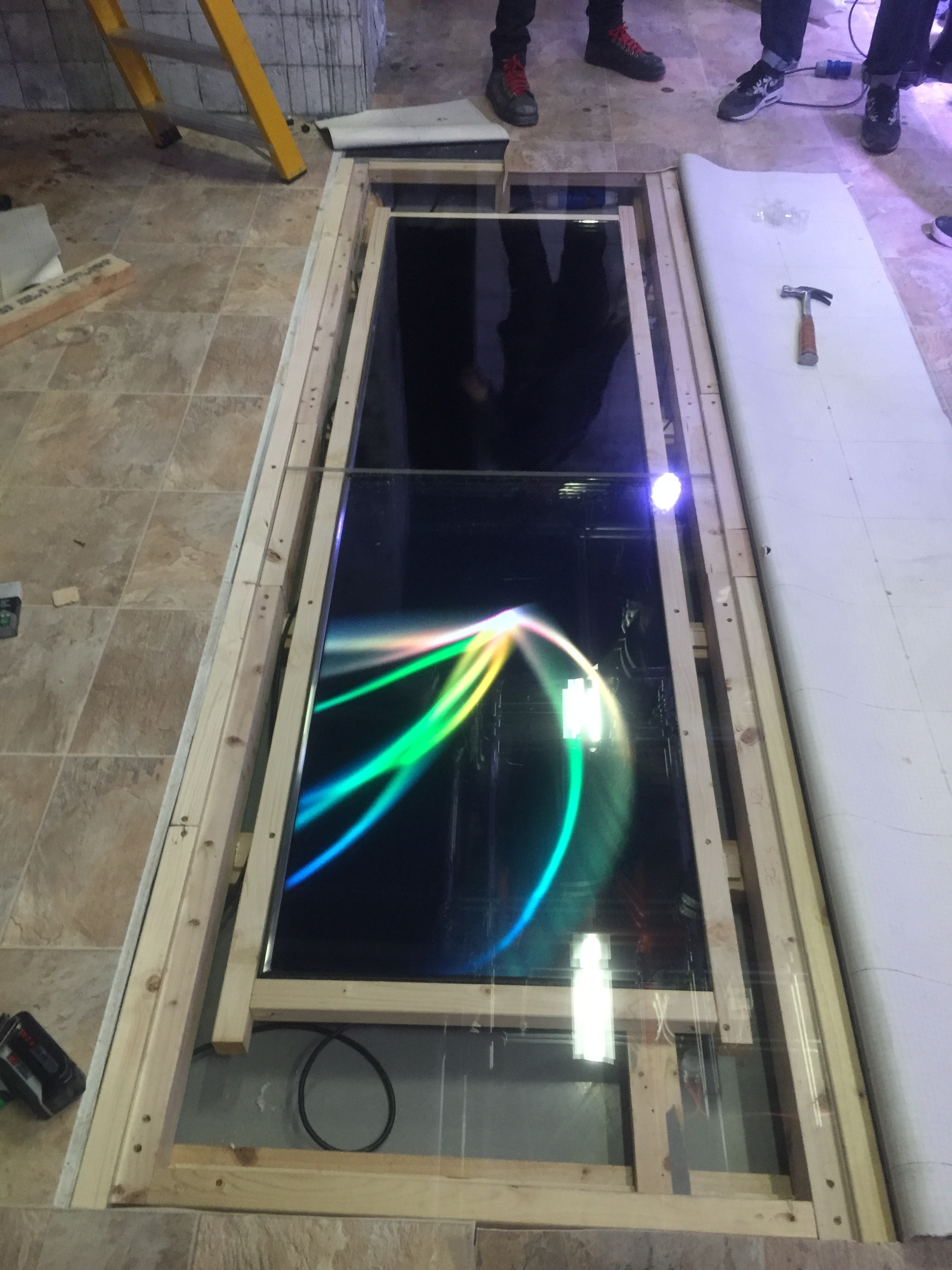 Tv screens being fitted in wooden frame.