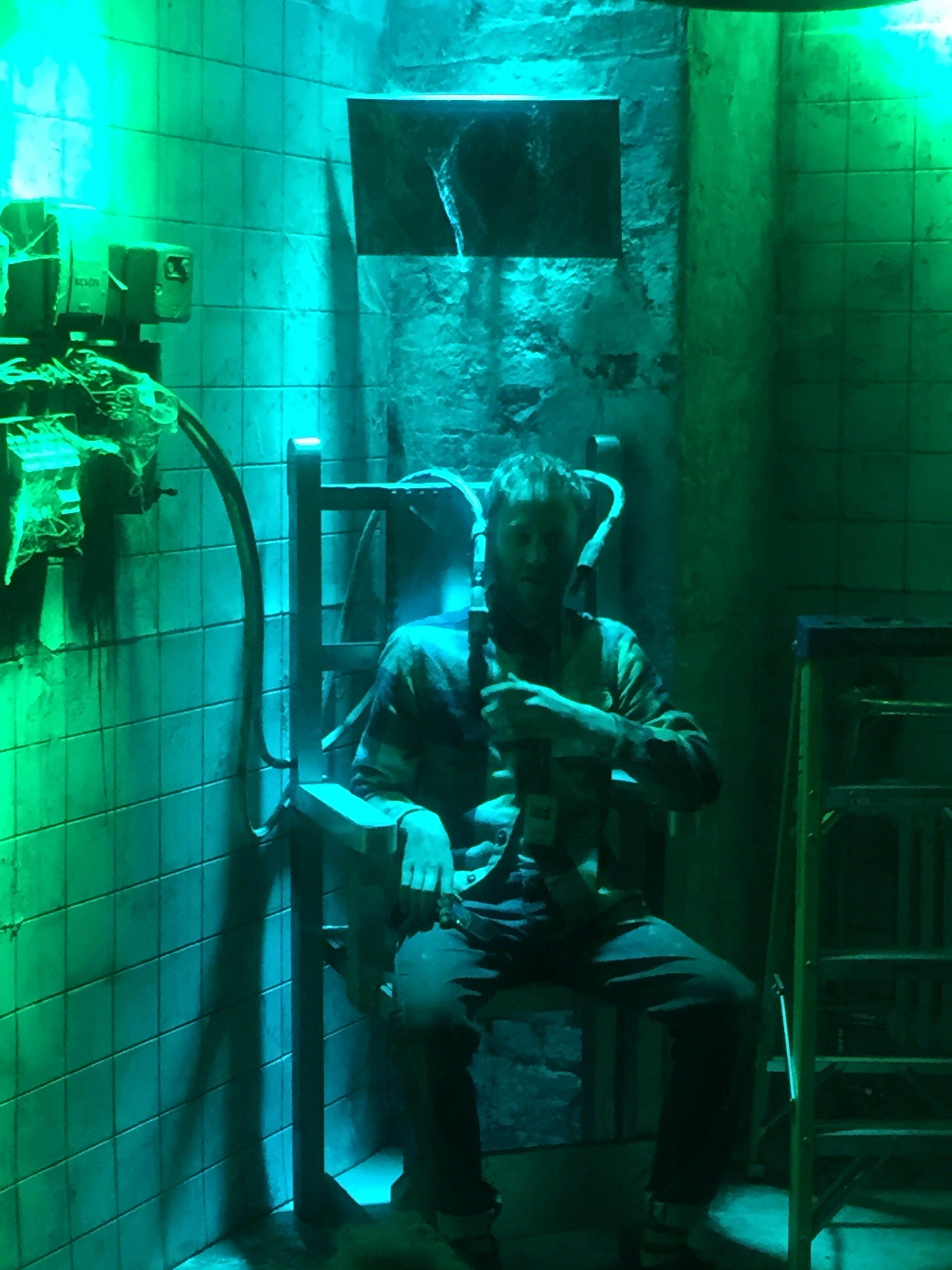 man lit in green and blue on electric chair.