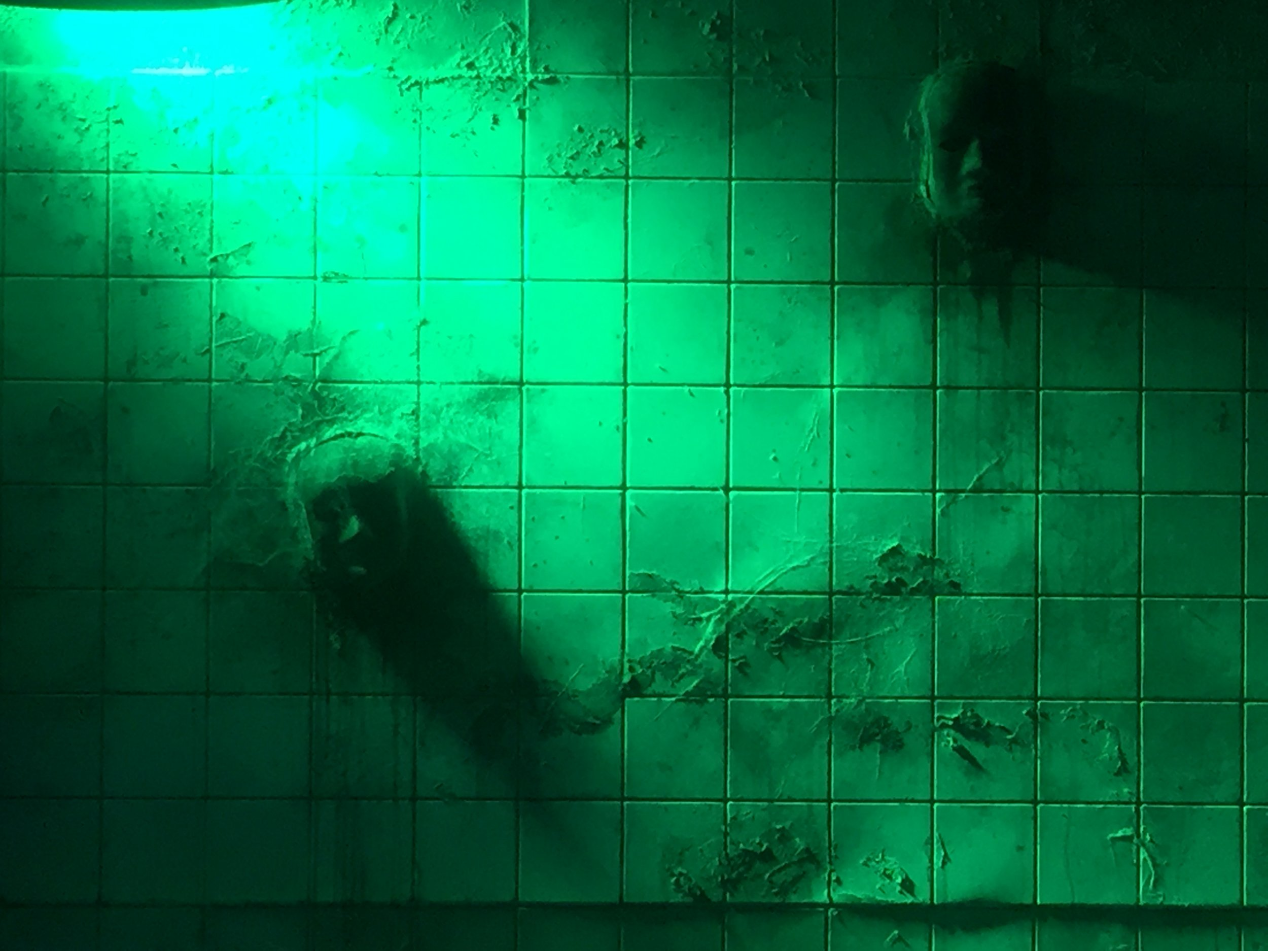 Faces coming out of the wall lit in blue and green.