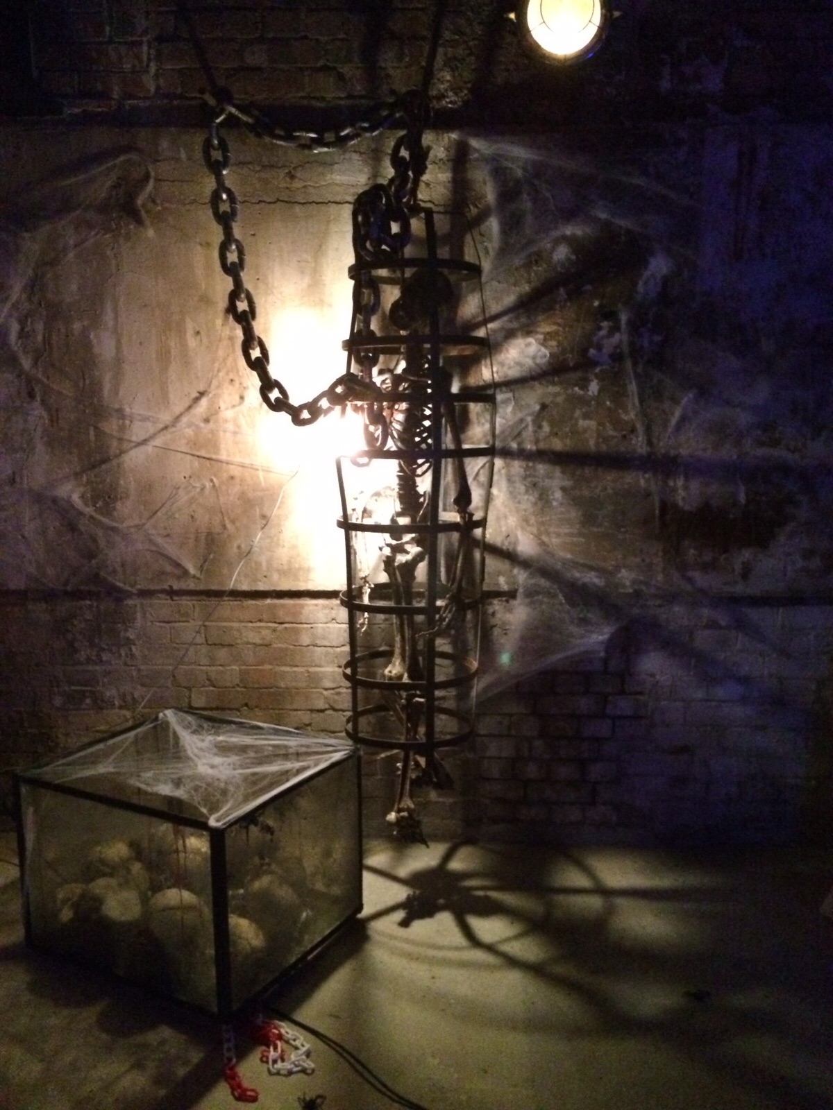 skeleton in rusted cage with yellow light behind.