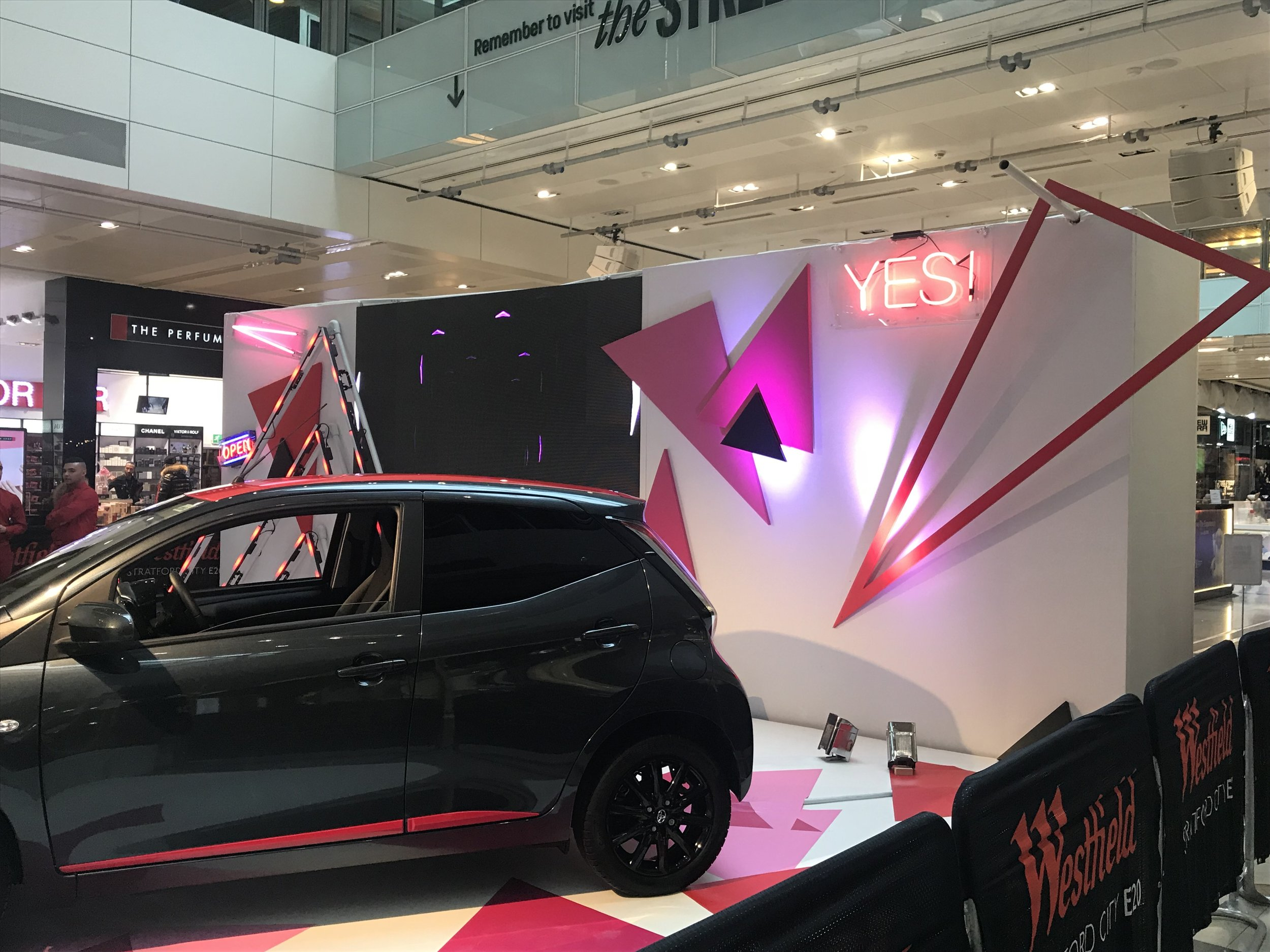 Toyota car with pink triangles behind it.