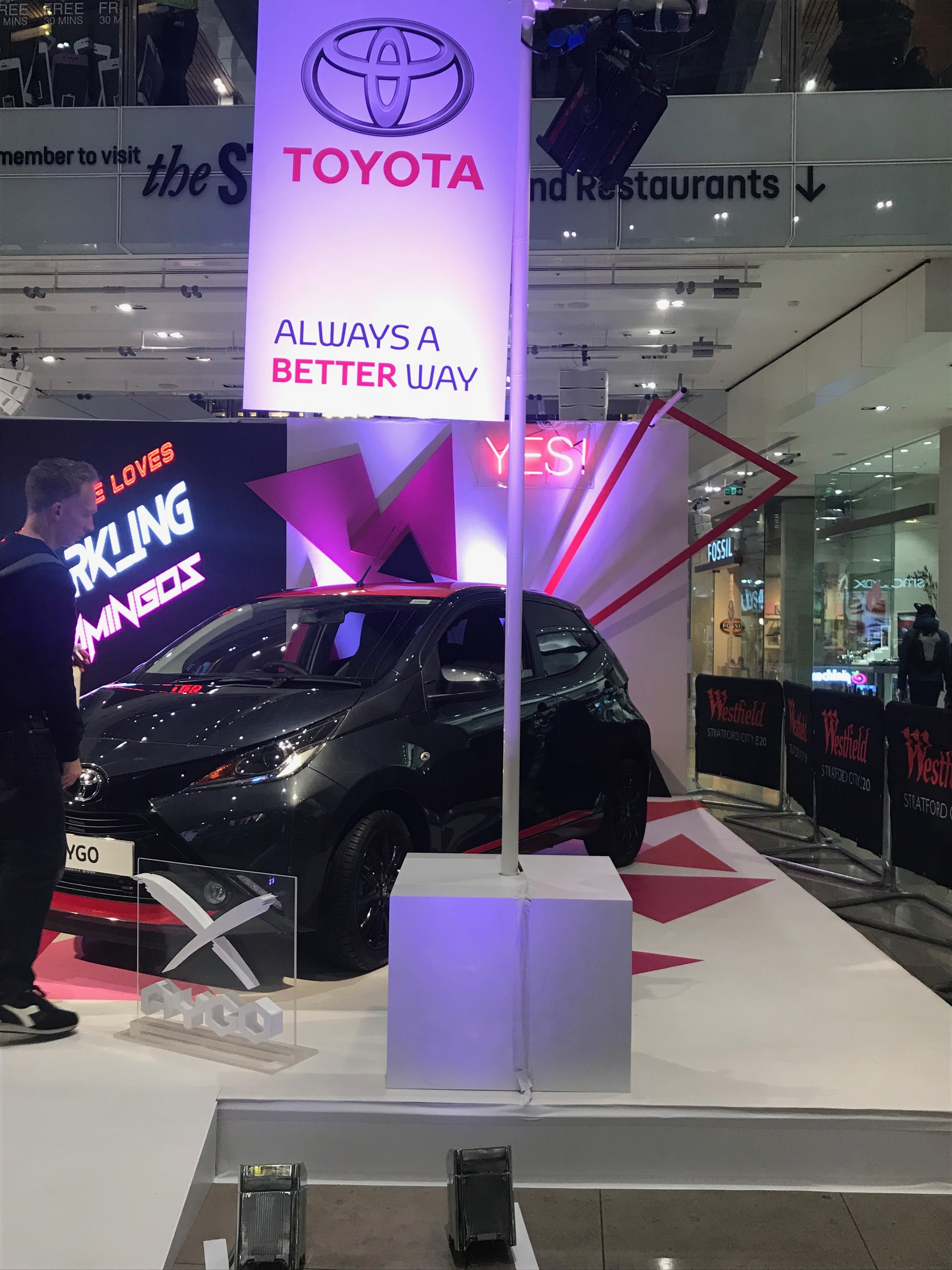 Toyota car with pink triangles and white lights.
