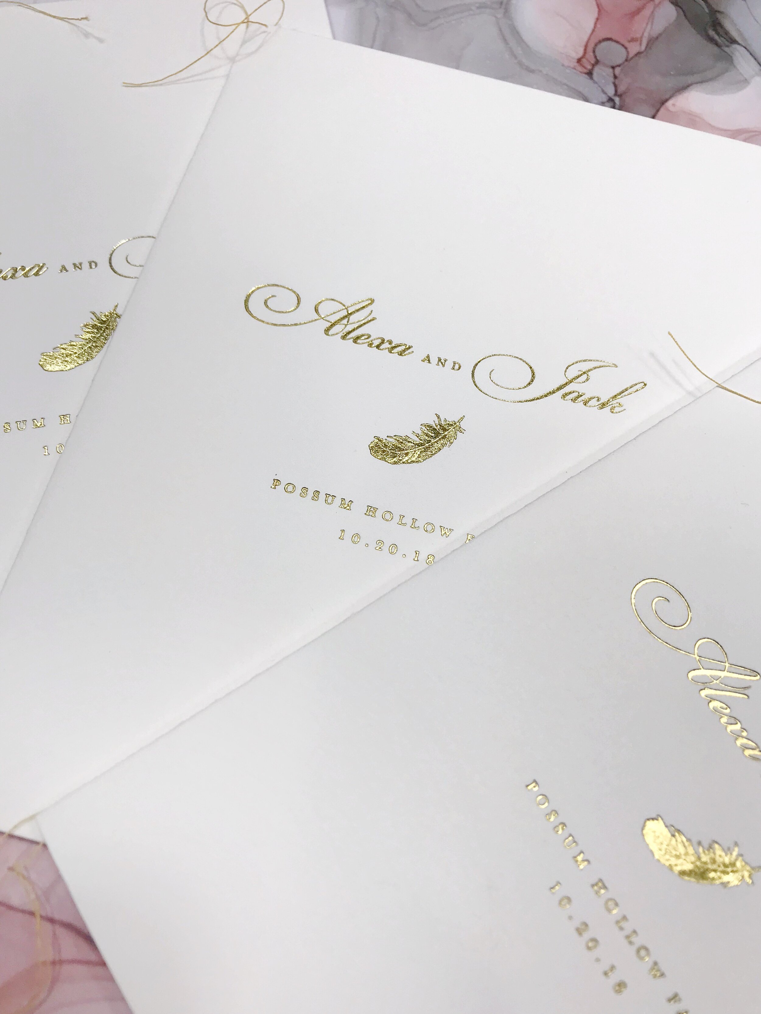Wedding program with gold foil and feather motif by Poeme
