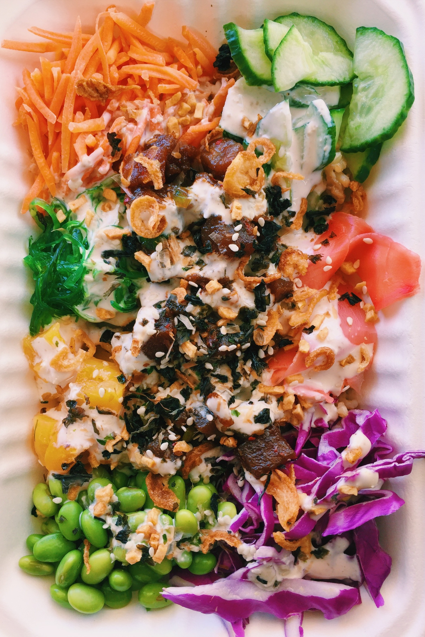Sesame Tuna - Edamame, cucumber, purple cabbage, carrots, pickled ginger, seaweed salad, peaches, and tuna topped off with our Sesame Aioli sauce, fried onions, fried garlic and furikake.