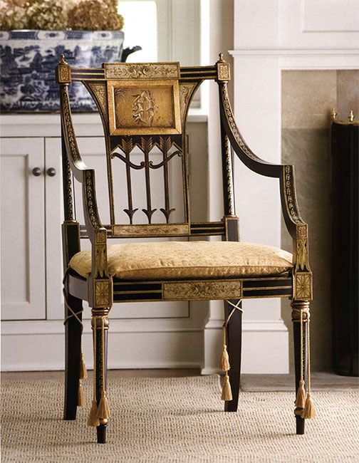Hand-painted Sheraton style armchair in antiqued black and gold finish, cane seat and upholstered cushion