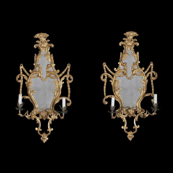 A fine pair of Rococo carved gilt wood cartouche form Girandole two – arm sconce mirrors. Having carved acanthus and bellflowers. England, 18th Century.